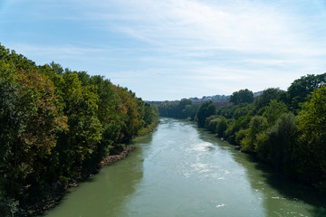 The Tiber river flows along with trees in sunny day, Rome, Italy.