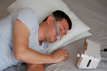 Close-up of young adult man wearing under the nose nasal mask ( CPAP mask ) and using CPAP machine for sleeping smooth without snoring.