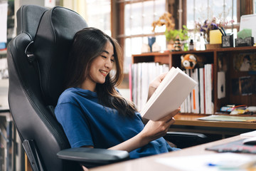 Happy smile young adult freelancer asian woman reading a book on relax in workplace at home.