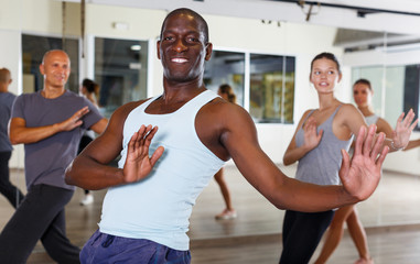 happy adult dancing people practicing vigorous swing in dance studio