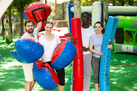 Portrait of happy friends with inflatable logs and pillows at an amusement park. High quality photo