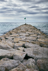 Breakwater of rocks with a green flag at the end