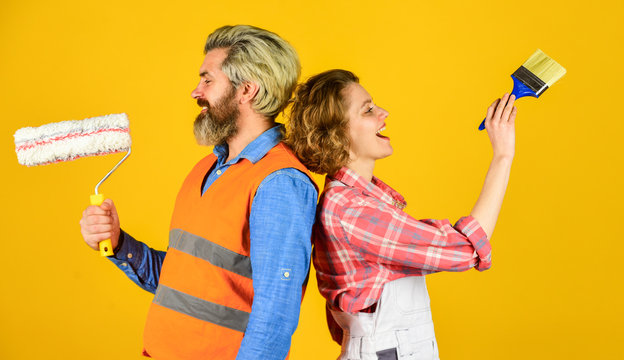 Painting walls. Cheerful couple renovating house. Woman builder. Man painter or decorator. Interior renovation. Decorating apartment. Pick color. DIY repair. Construction workers. Home renovation