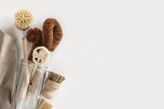 Zero waste kitchen cleaning concept. Eco friendly natural cleaning tools and products, bamboo dish brushes, towel, glass jar, natural soap No plastic, eco-friendly lifestyle. Top view, flat lay.