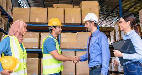 Group of Diversity warehouse worker hand shaking when success the agreement together in local warehouse, muslim with Hijab, indian, white caucasian and asian people in export industry concept