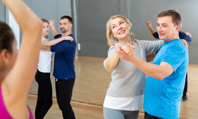 Cheerful middle aged woman learning to dance waltz with partner in dancing class