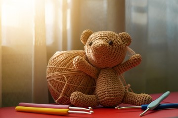 Handcrafted cute crochet brown bear doll using polyester yarn, amigurumi knitted bear doll with crochet hooks on red table