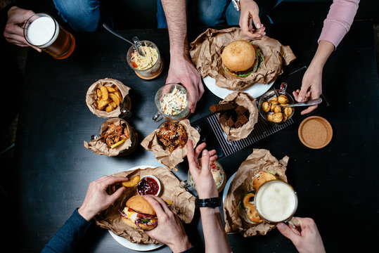 Great menu for beer party with friends. Burger, sandwich, salad, french fries, bread croutons, meat dumplings, fried shrimp, pasta, fried chicken on black table