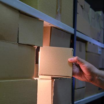 Man takes a box from a warehouse at night