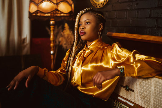 African American fashionable woman with many braids hairstyle, wearing stylish yellow blouse, posing in dark vintage luxury interior. Copy, empty space for text
