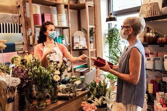 Young female florist with mask working in flower shop, selling flower arrangement to senior woman.