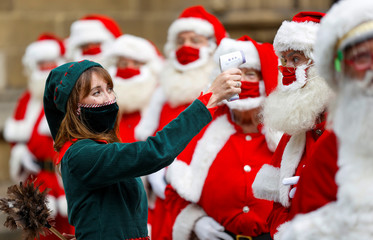 A woman dressed as an elf poses for a photo with attendees of the Ministry of Fun Santa School outside Southwark Cathedral in London