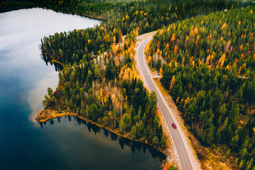 Aerial view of rural road with red car in yellow and orange autumn forest with blue lake