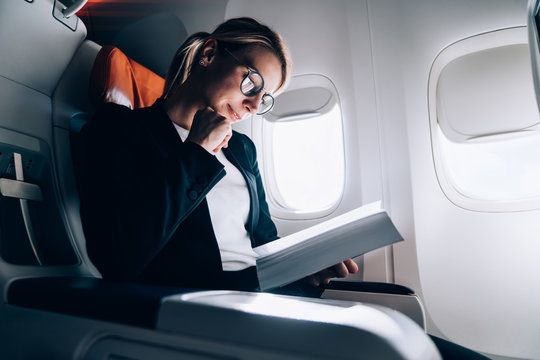 Cheerful relaxed lady reading book in contemporary plane