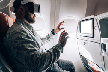 Millennial male airplane passenger playing 3d game during jetliner flight testing artificial world via advanced applications and VR digital goggles, man touching haptic dimension during projection Fotobehang