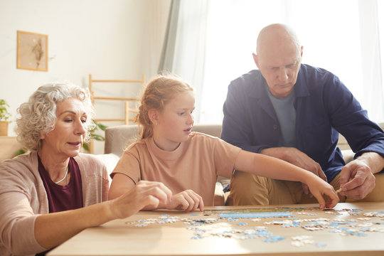 Portrait of cure red haired girl playing board games with grandparents while enjoying time together in cozy home lit by sunlight