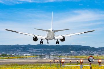 伊丹空港に着陸する旅客機 Fotobehang