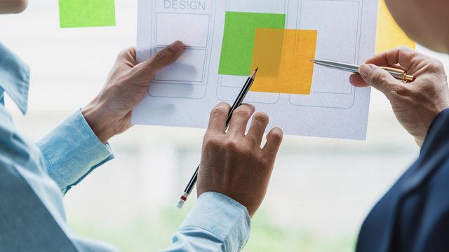 Designer men pointing stick note planning develop application develop for mobile phone.