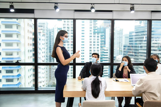 Young businesswoman and business man wearing protective face mask whilemeeting for making new business plans during COVID-19 pandemic