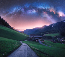 Arched Milky Way over the rural mountain road in summer in Italy. Beautiful night landscape with...
