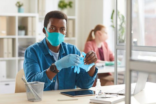 Portrait of young African-American man wearing mask and gloves looking at camera while working at desk in cubicle at post pandemic office, copy space