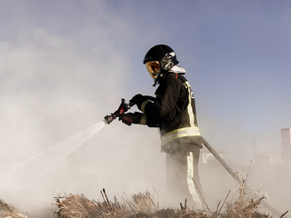 Firefighter spraying water on wildfire