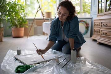 Female artist creating artwork on floor
