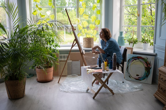Artist with wine sitting near easel