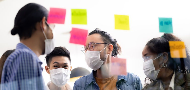 Interracial business team wear face mask brainstorm at new normal office Panorama