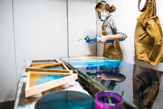 Female resin working in homemade studio with blowtorch