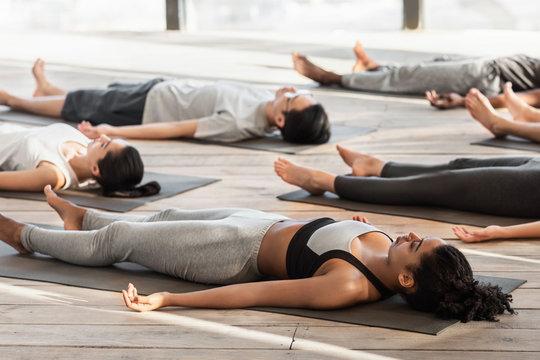 Savasana Pose. Diverse Yoga Class Members Meditating On Floor, Lying On Mats