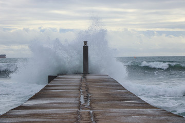 big ocean wave hit in a jetty in a stormy day