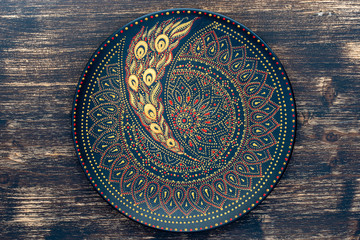 Decorative ceramic plate with black, red and golden colors, painted plate on wooden background , dot painting