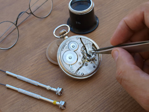 vintage pocket watch under repair, with exposed mechanism, eye glasses and magnifier over wood table