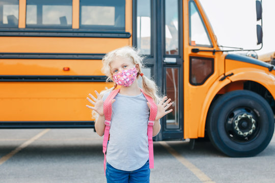 Happy Caucasian girl student wearing face mask near yellow bus. Kid with personal protective equipment on a face. Education, back to school in September. New normal during coronavirus.
