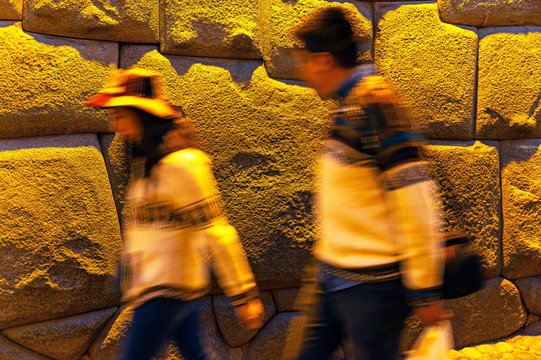 Tourists passing by the Twelve Angle Stone in the Hatun Rumiyok street at night, Cusco, Peru.