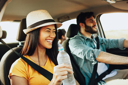 Family trip. Latin family traveling locally by car. Man drives the car, woman holds a bottle of water