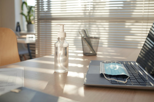Background image of face mask and hand sanitizer on empty workplace desk in post pandemic office lit by sunlight, copy space