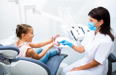 Cute little girl sitting on a dental chair having fun with a positive dentist. Kid teeth treatment