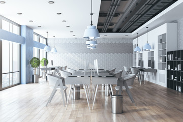 Bright coworking office interior with furniture and daylight.