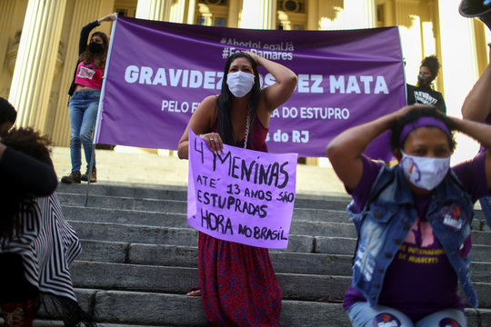 """A member of a feminist collective holds a placard reading: """"4 girls up to 13 years old are raped every hour in Brazil"""" as she attends a protest, in Rio de Janeiro"""