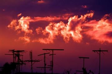 Antenas no telhado e o céu avermelhado