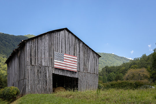An old barn with an American flag painted somewhere in the mountains on a sunny day