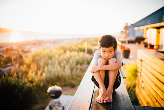 Portrait of boy by the sea at sunset