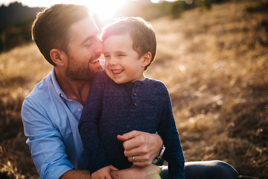father holding son smiling in a field with golden light