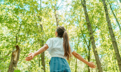 Fototapeta Free woman breathing clean air in nature forest. Happy girl from the back with open arms in happiness. Fresh outdoor woods, wellness healthy lifestyle concept. obraz