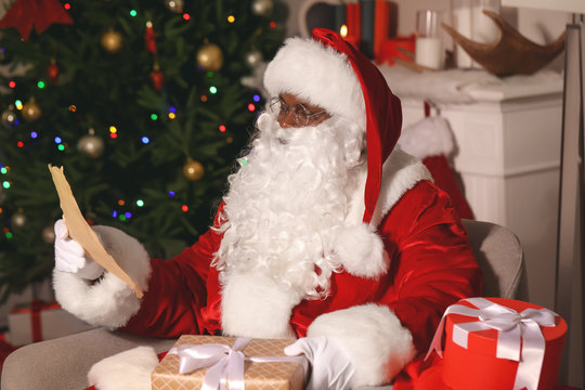 African-American Santa Claus reading wish list in room decorated for Christmas