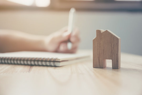 Close up hand of man take notes in a notebook plan to be a landlord with wooden house model. Mortgage and real estate property investment
