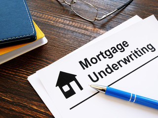 Information about mortgage underwriting and pen on the table.