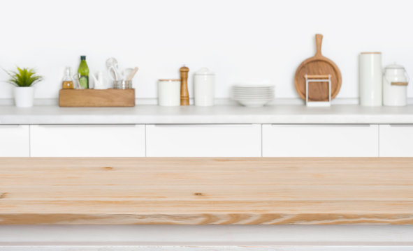 Board in front of kitchen countertop with utensils and spices
